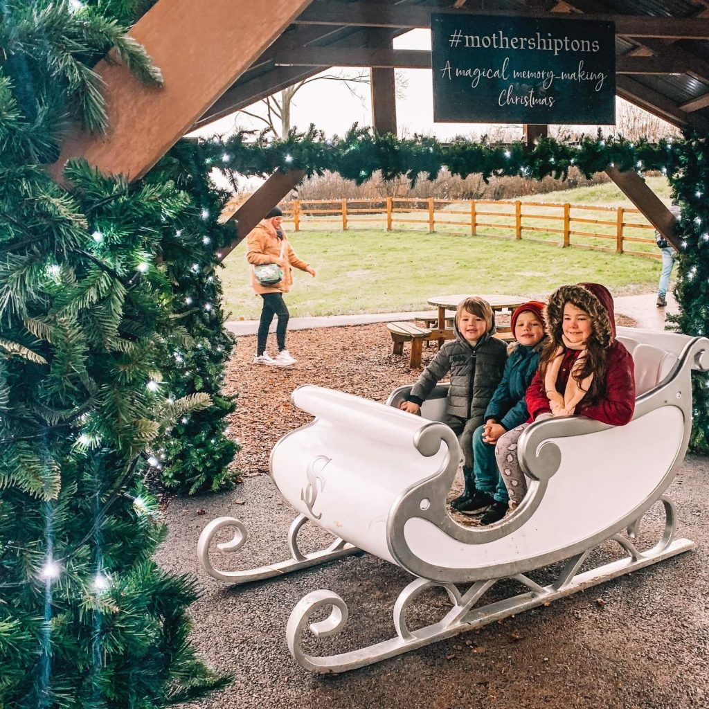 three children sitting in a white sleigh with silver trim and silver 'S''C' lettering on the front, underneath a wooden canopy adorned with green Christmas garlands and christmas lights, a sign above them says '#mothershiptons A magical memory-making christmas'