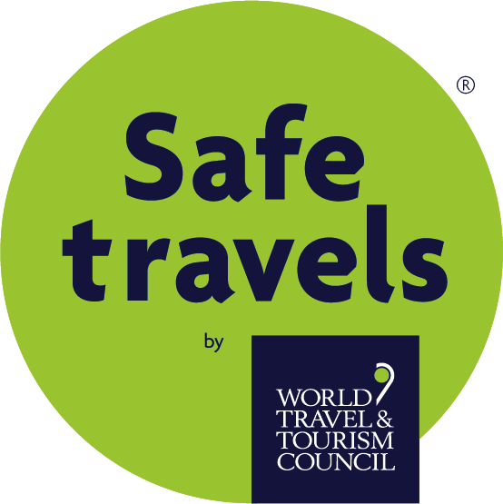 Safe Travels logo from the World Travel & Tourism Council, the logo is a green circle with dark blue text.